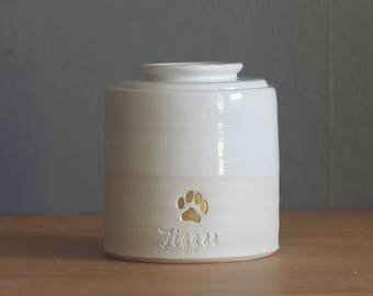 custom urn with lid. shown with optional gold stamp and script font. straight shape urn, paw stamp. modern simple urn. white and gold urn.