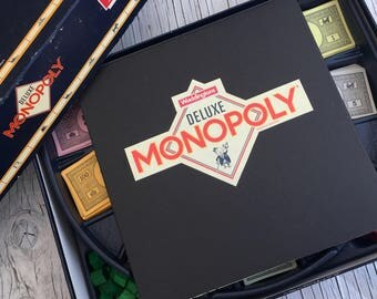 Vintage Deluxe Monopoly, complete set with rules, wooden houses and hotels, gold colour pieces, rack for London properties, hardly used.