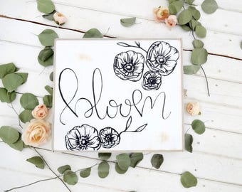 bloom with floral print  black and white rustic wood sign