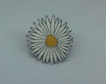 A large white and yellow daisy flower enamel brooch pin