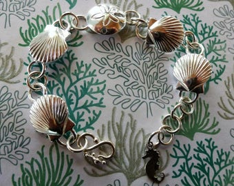 Silver Seashells By The Seashore Bracelet - sterling silver scallop shells center a sand dollar and dangle a seahorse charm. S-hook clasp.