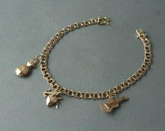 Mid century romantic detailed charm bracelet, 14 karat solid gold.
