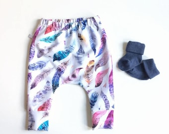 Baby infant pants with feathers. Slim fit harem pants with cuffs. White sweat fabric with pink and blue. Infant sweat pants. Bbaby leggings