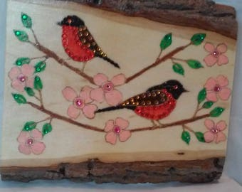 Wood burned plaque with red robins in a pink dogwood tree painted, glazed and embellished with colored crystals