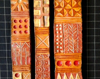 Triptych - 3 long ceramic tiles with carved & painted patterns glazed in red, olive, and gold.