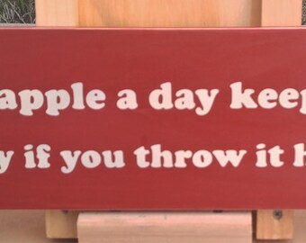 An apple a day keeps anyone away if you throw it hard enough wooden sign