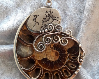 Artfully framed Ammonite in 925 sterling silver with stone-age hunting scene