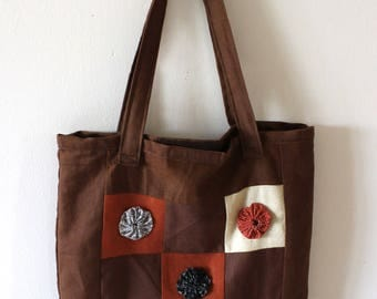 a hand made shoulder bag in heavy cotton with yo yo technique details