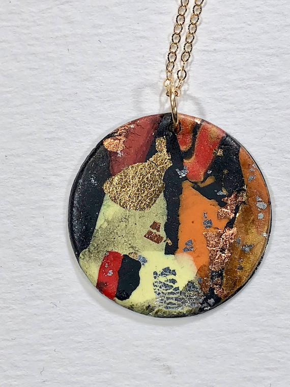 Handmade orange/red/yellow/black/ocre/gold/silver/copper polymer clay round pendant necklace with abstract asymmetric design