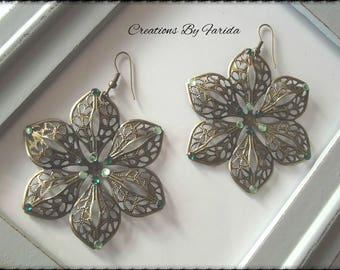 Bronze earrings dangle a flower with 6 petals with green rhinestones