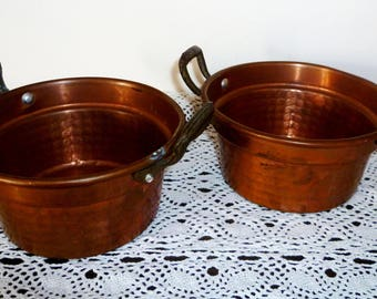 A pair of copper saucepans/a couples of copper pots