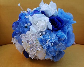 Disney cinderella themed wedding bouquet. Baby blue, royal blue and ivory bouquet with Cinderella shoe brooch and butterfly brooch