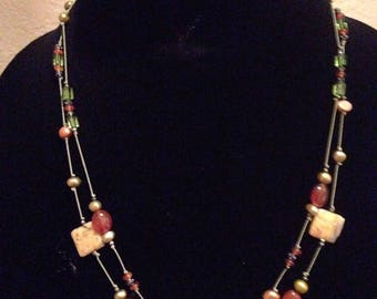 Gemstones on a knotted silk necklace and earrings .