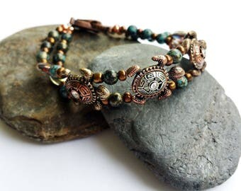 Turtle bracelet with nautical and glass bead accents with magnetic fold over clasp in Copper metal tones.