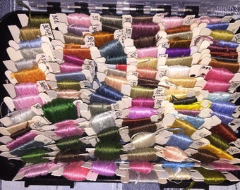 Embroidery floss on bobbins in storage container