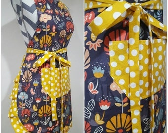 Adult apron. Woman's apron. Bright yellow, blue, and coral floral on main. Yellow with white polka dots on pocket, ties and frills.