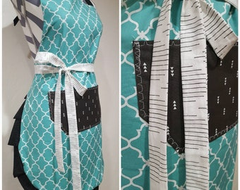 Adult apron. Woman's apron. Darker teal on main.  Black pocket with mini arrows. Ties white with black lines. Frills black with polka dots.