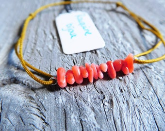 Tiny red coral bamboo on a silver and coton sliding knot bracelet