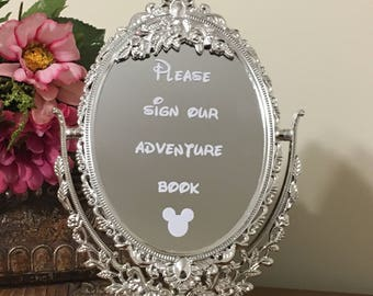 Ornate mirror with decal inscription/Please sign our adventure book mirror sign