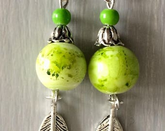 Earrings green glass bead and feather charm