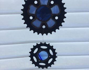 Stained glass sun catcher.  Bike sprockets with blue glass.