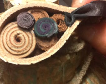 Leather pendant with concentric circle patter and swirl symbols and earthy boho style