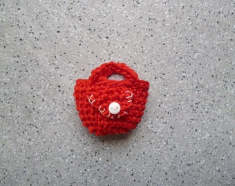 1 miniature bag decorated with red cotton crochet with a small white button