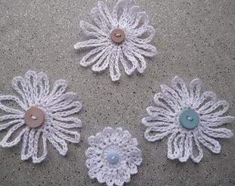 4 white crochet flowers in white cotton decorated with a button