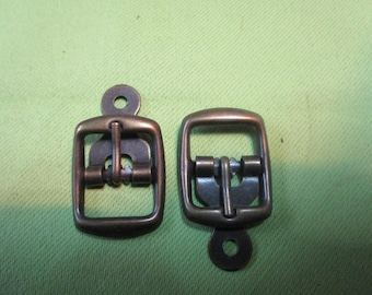 small metal buckle has bronze chappe