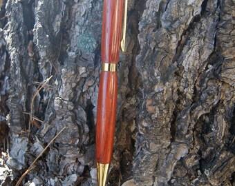 Black ink ballpoint pen turned by hand in Padauk wood