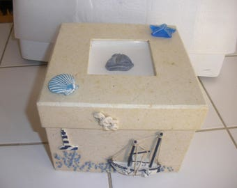 Cardboard box and natural unbleached paper featuring a sailor boat in resin and seashells in resin with lid.