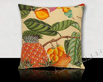 Square cushion exotic fruits pineapple/mango/papaya in spicy shades of orange/yellow/green/blue on pale yellow background.