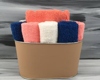 Tan Bathroom Towel/Wash Cloth Bin with  1 orange hand towel, 3 dark blue wash cloths, 3 peach wash cloths and 3 white wash cloths.