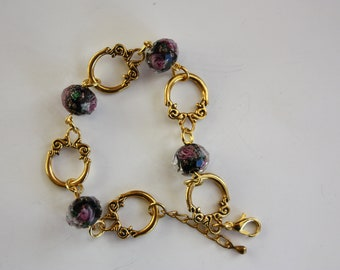 Pearls and gold tone bracelet has faceted black and pink