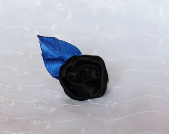 Black flower and its blue leaf on hair clip