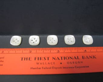 Five square white plastic buttons