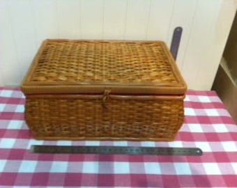 Wicker sewing basket with red interior.