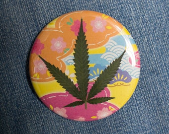 Pressed Cannabis Leaf Button On Bright Pink, Yellow & Orange Background