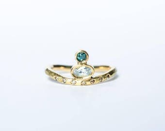alternative bridal womens engagement ring with white sapphire, blue diamond and champagne diamonds in 18k yellow gold