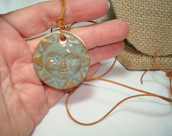 Handmade Ceramic Smiling Sun Necklace on a Leather Cord.