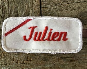 "Julien. A white work shirt name patch that says ""Julian"" in red script with white border"