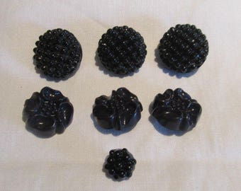 Riveted black glass mirror back buttons x 2; moulded floral navy celluloid buttons x 3; 2 extra black riveted buttons; Edwardian