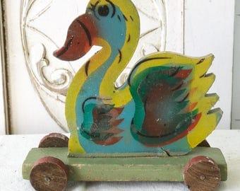 A fantastic primitive vintage painted duck on wheels