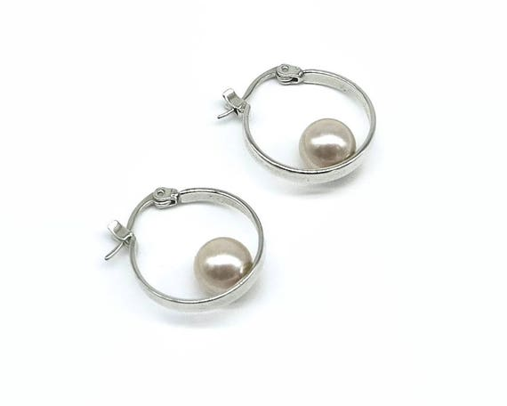 Silver hoop earrings with single large champagne colored pearl sitting in the bottom, top opening