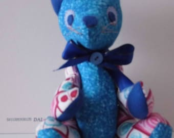This sweet bear is handmade and has unique qualities. He is a one off and is very colourful. I love the blue in him and his blue bow.