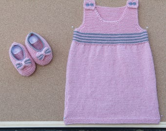 A hand knitted baby pinafore dress and matching shoes.
