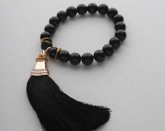 Bracelet with black agate, silk tassel and golden pendant. Natural stones 10 mm