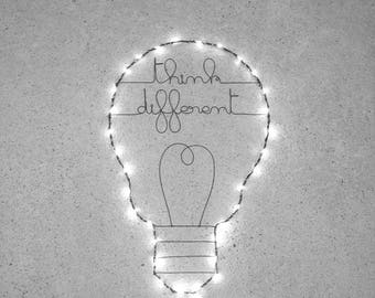 Light bulb, wall decoration, surrounded by a string of lights operated message writing in wire
