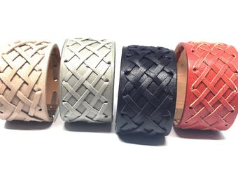 Wide braided leather bracelet with a silver metal clasp.