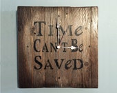 """Wall clock made with recycled wood decorated with """"Time can't be saved"""" label"""